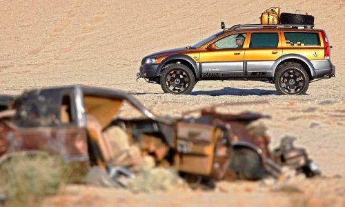 vehicle driving past rusty car body on beach